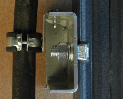 Morsetto ad anello con gomma antivibrante per fisssaggio tobo flessibile di mandata dell'olio montato su staffa guida.