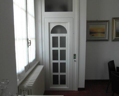 Porta a battente per ascensore con finestra tipo inglese.